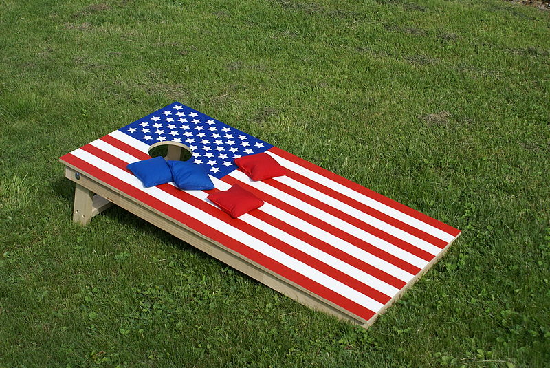 Cornhole board with an American flag decoration.