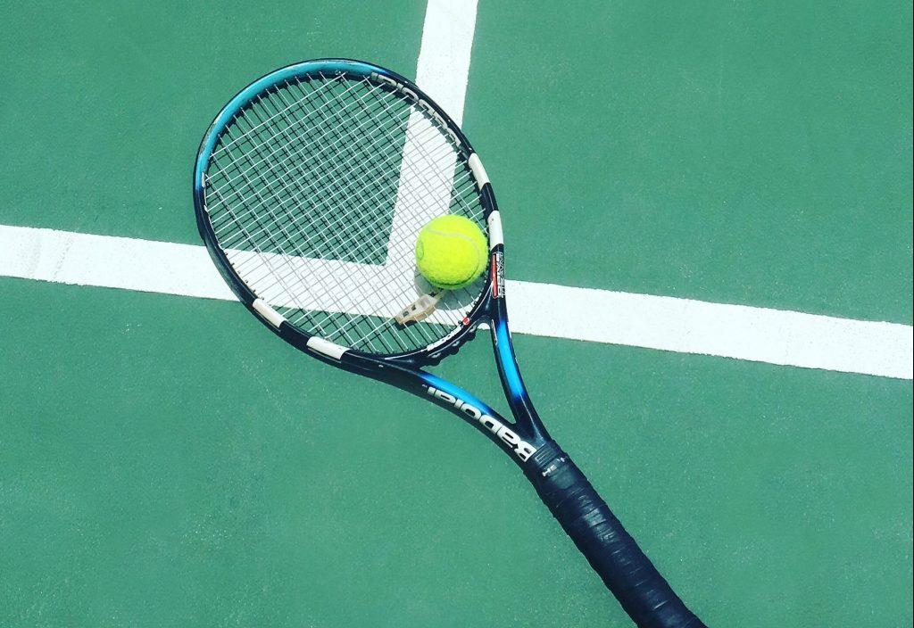 Babolat tennis racket with vibration dampener installed.