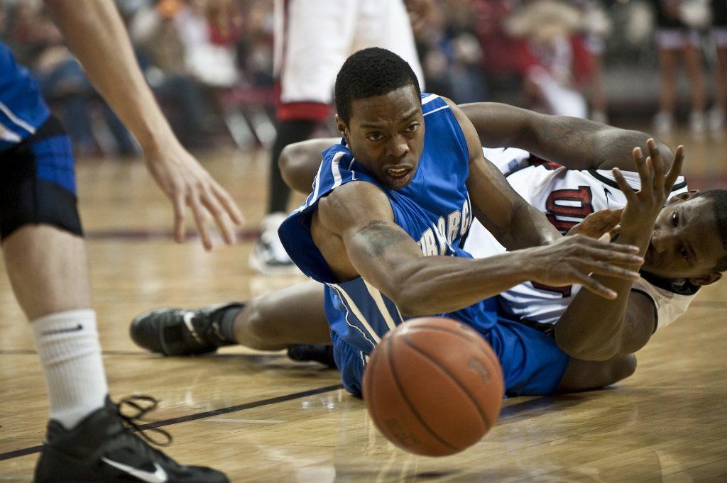 Basketball players contesting a ball.
