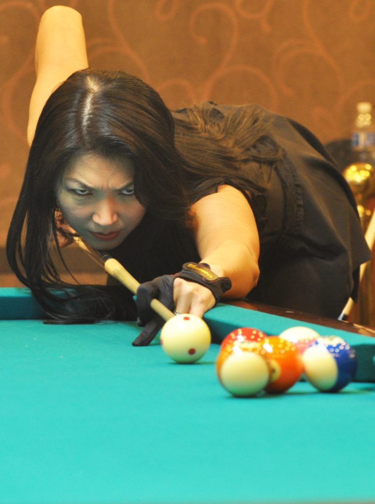 Jeanette Lee AKA The Black Widow using a pool glove.