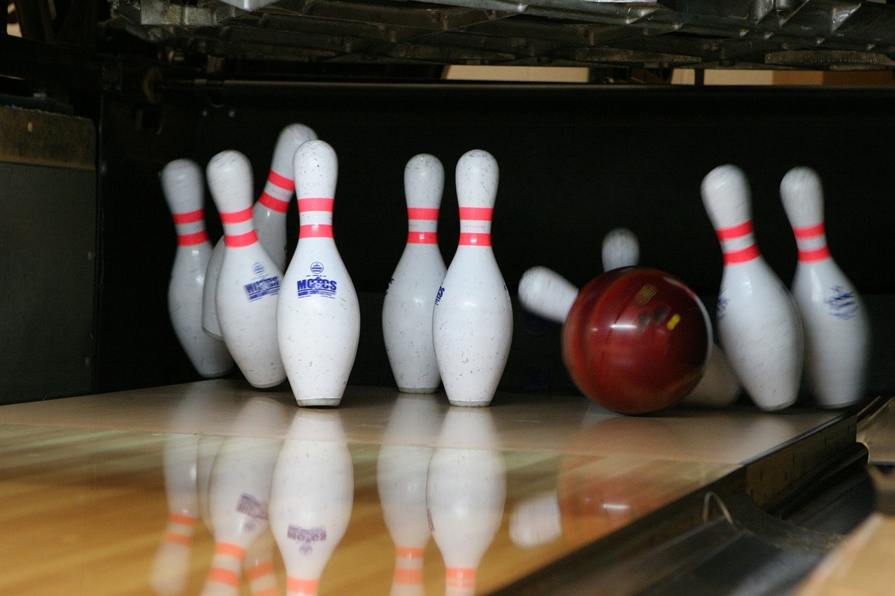 Bowling ball knocking over some bowling pins.