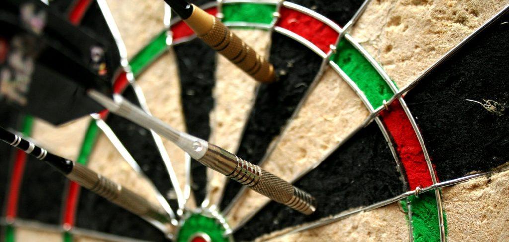Bristle dartboard with darts in it.