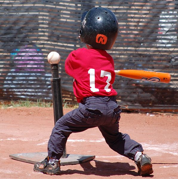 A tee-ball player using a batting tee.