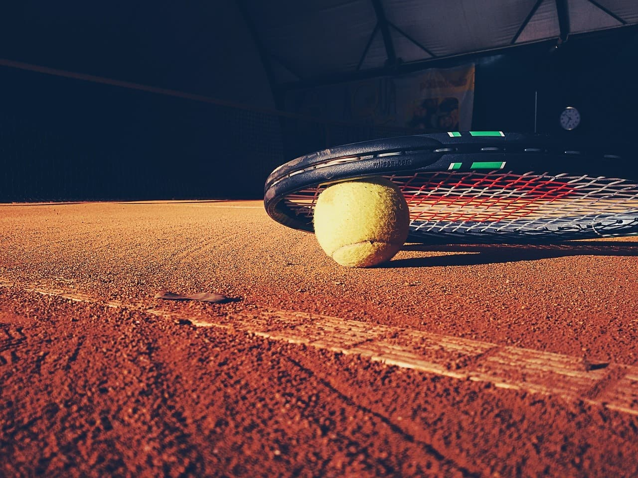 Tennis ball and racket resting on a clay court.