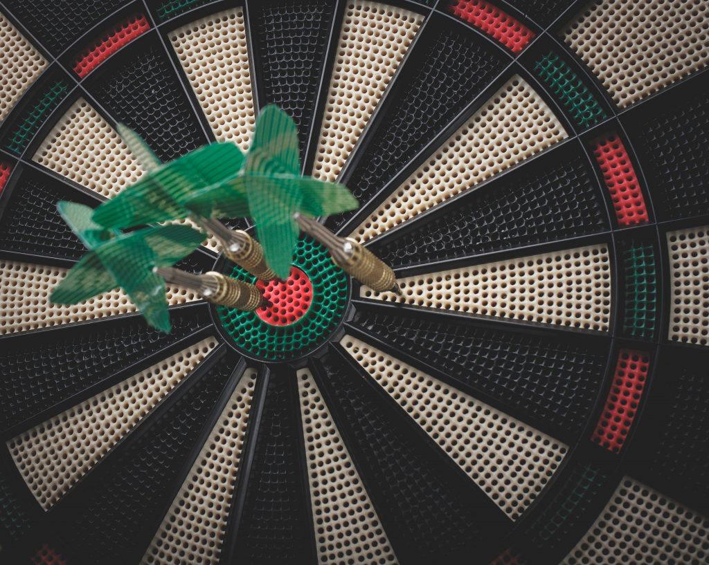 Electronic dartboard with three darts in it.