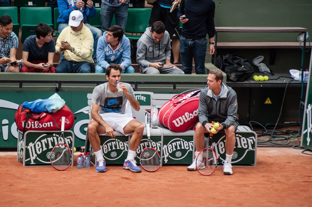 Roger Federer and coach Stefan Edberg with the tennis player's tennis bags and equipment.