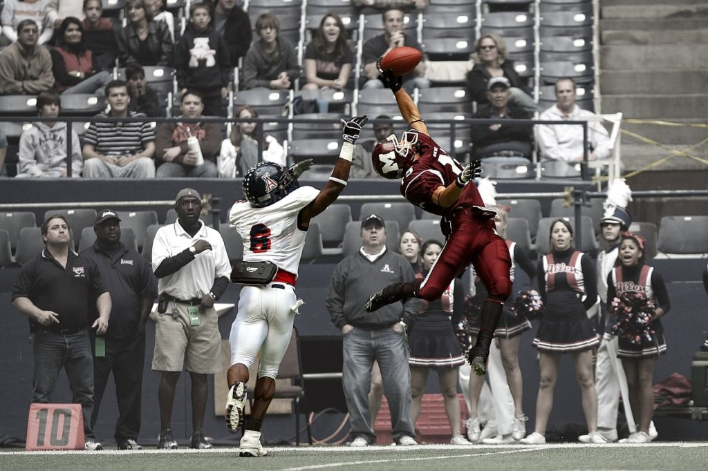 American football receiver taking a jumping catch.