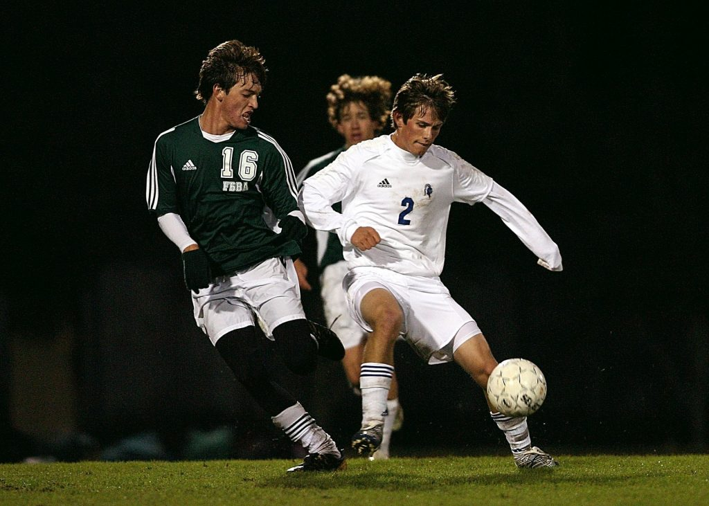 Two high school soccer players challenging for the ball.