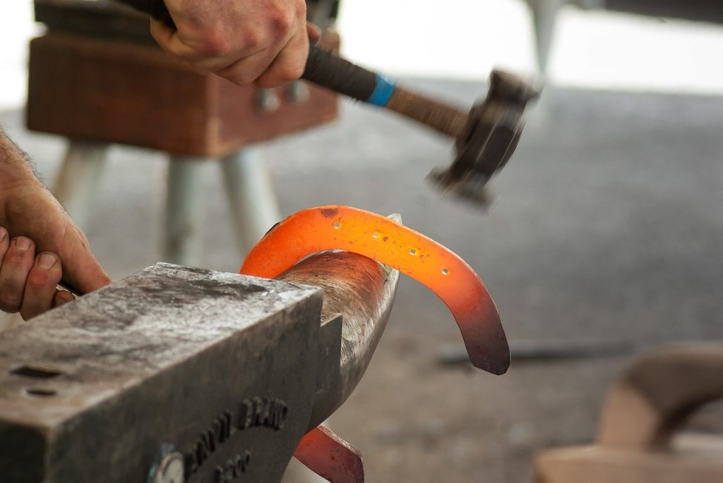 A horseshoe being forged by a blacksmith.