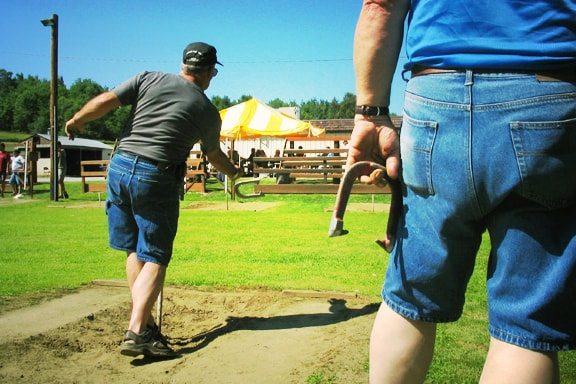 People playing a horseshoe toss game.