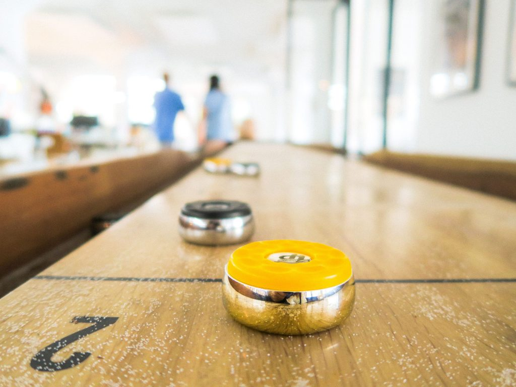 Indoor shuffleboard table with shuffleboard weights on it.