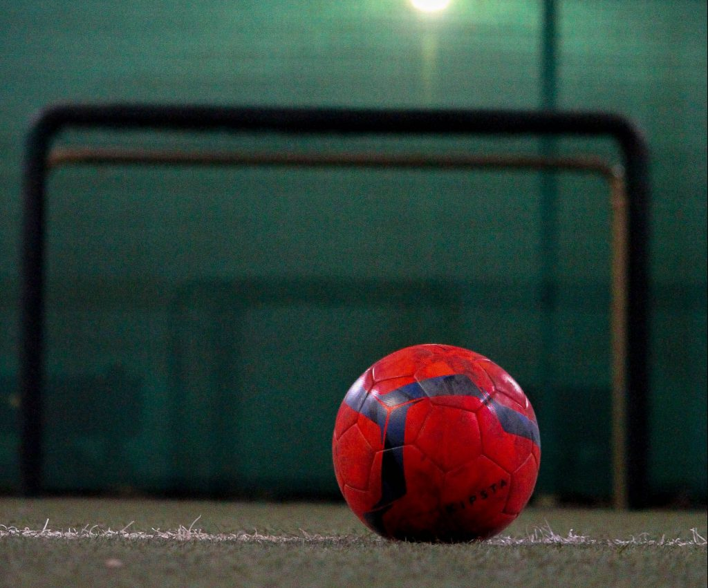 A soccer ball on an indoor soccer pitch.