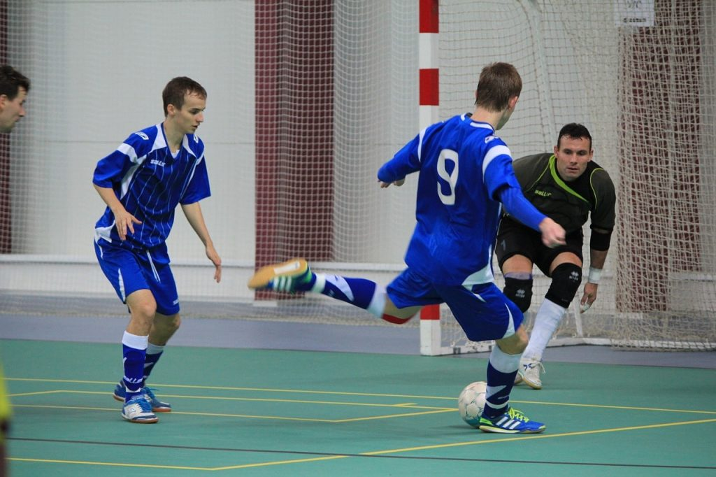 Soccer players playing futsal indoors.