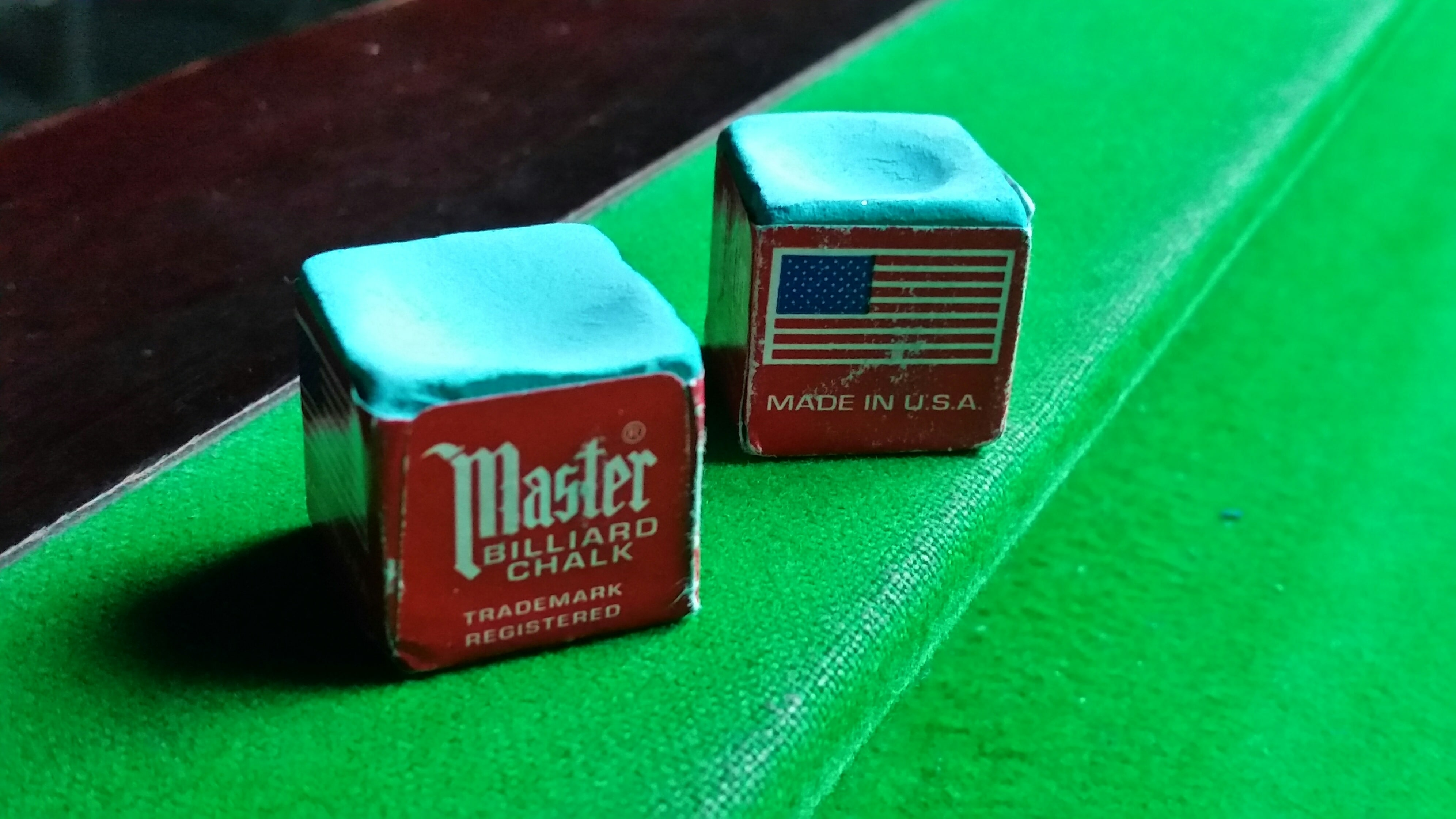 Master chalk resting on a pool table cushion.