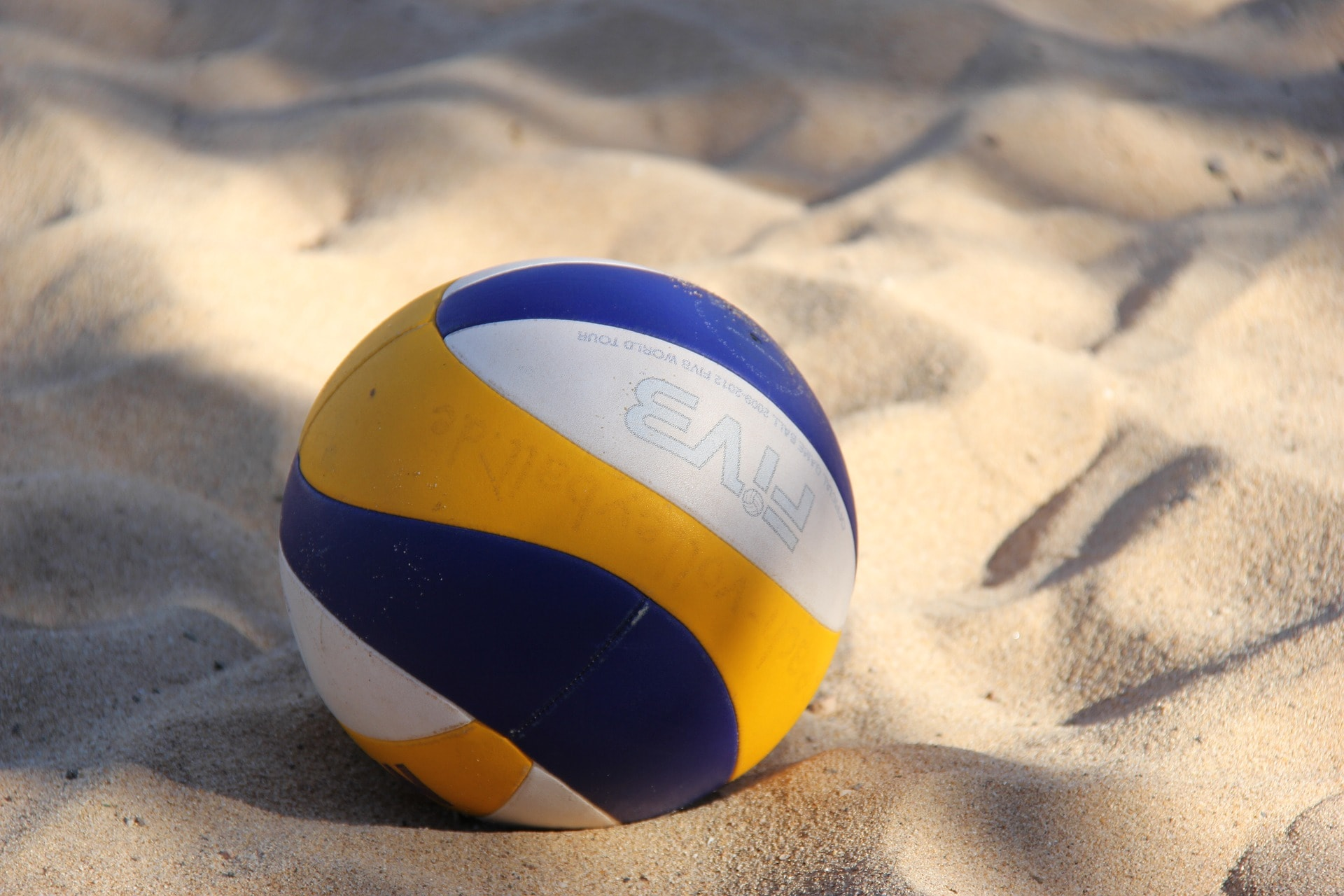 Beach volleyball resting on sand.