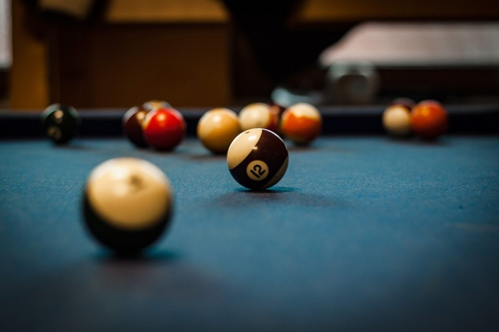 A blue pool table being used.