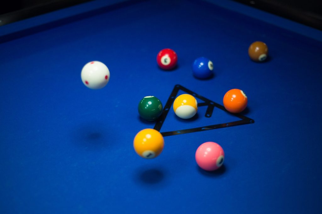 Pool balls on a woolen pool table surface.