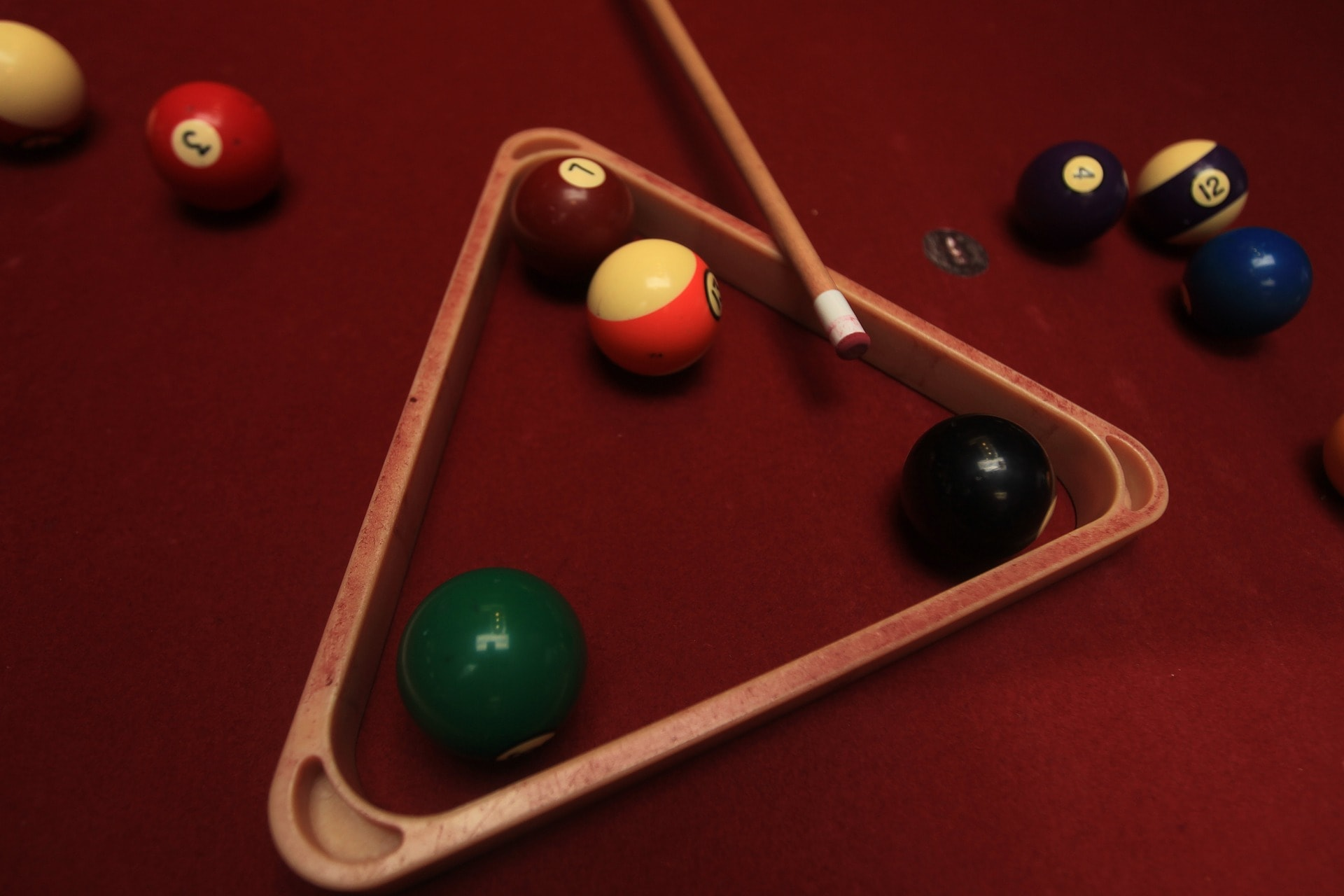 Pool balls and a pool cue resting on a pool table.
