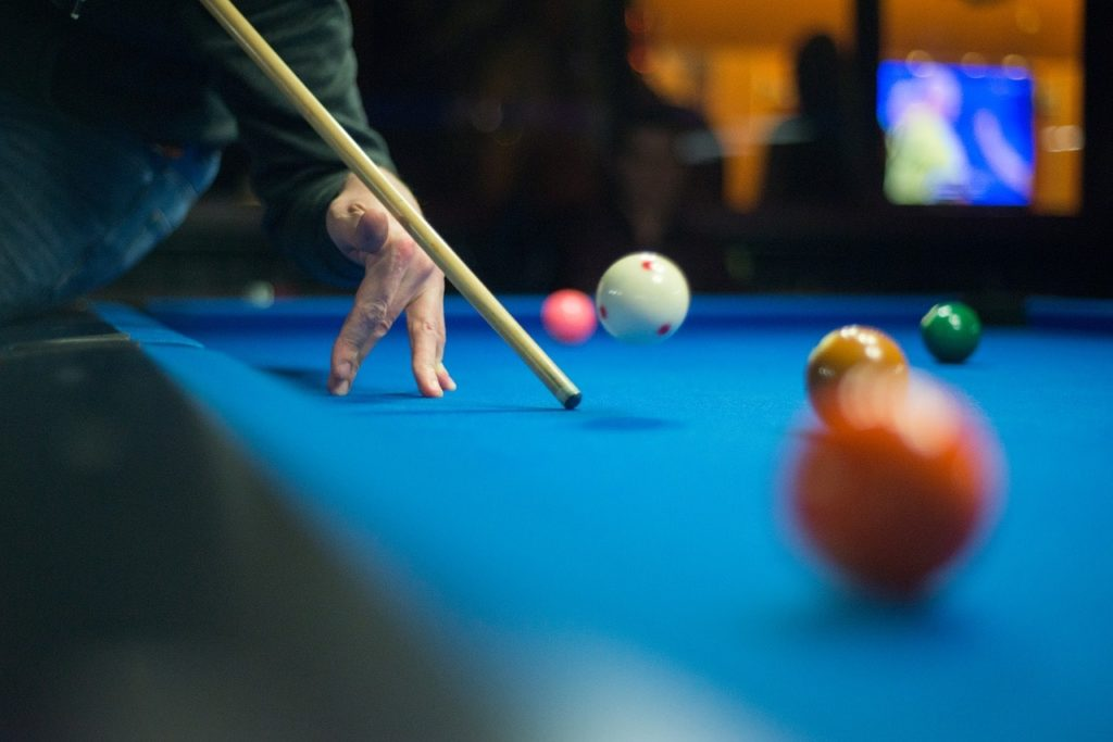 A pool player playing a jump shot.