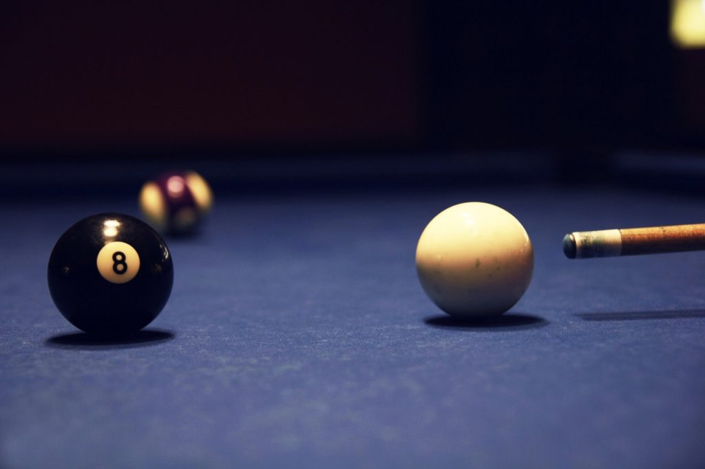 A pool cue about to strike the cue ball into the 8 ball.