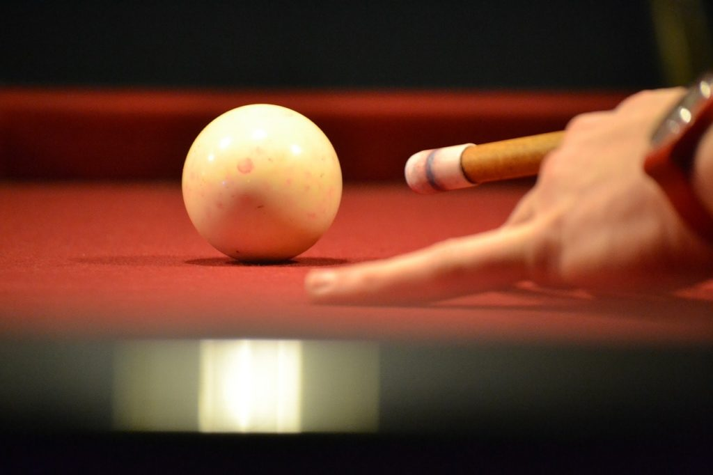 A pool player using a pool cue to strike the cue ball.