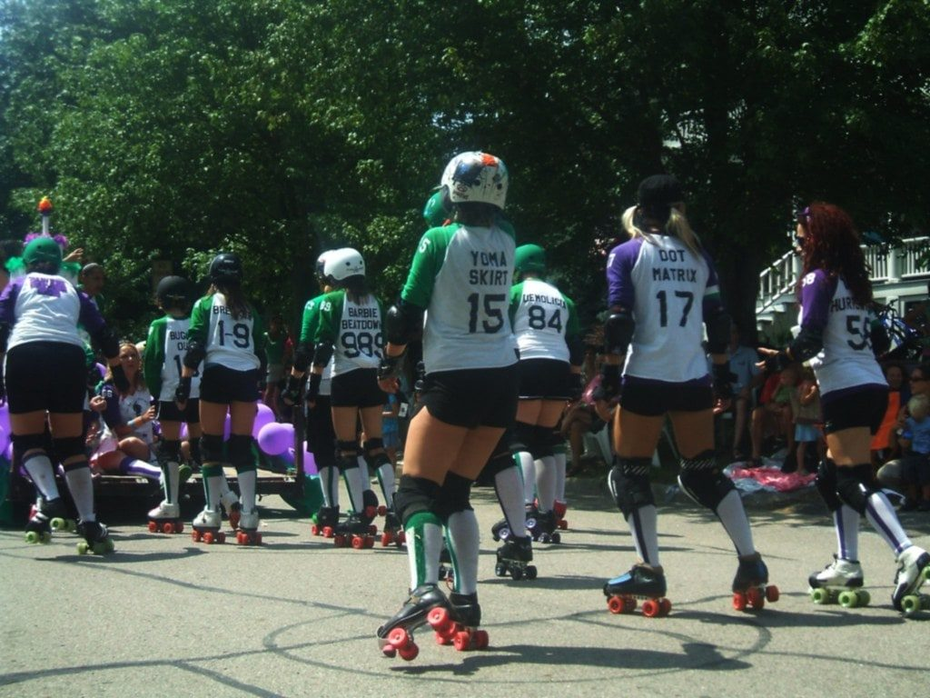Girls playing roller derby outdoors.
