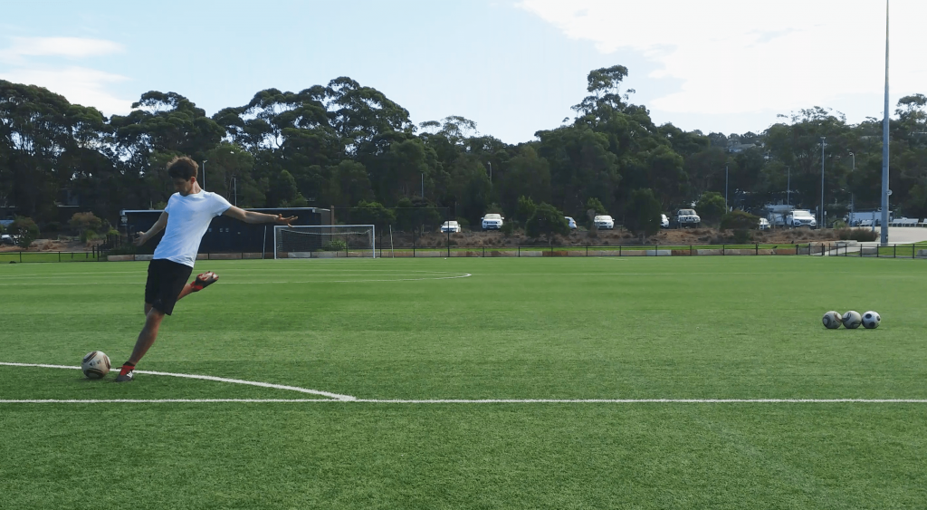 Striker shooting a soccer ball.