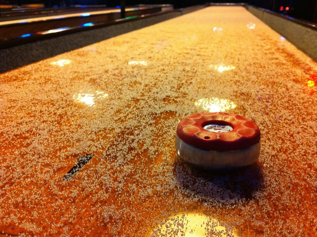 Shuffleboard puck on a shuffleboard table.