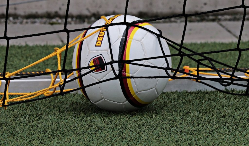 Soccer ball in a soccer goal.