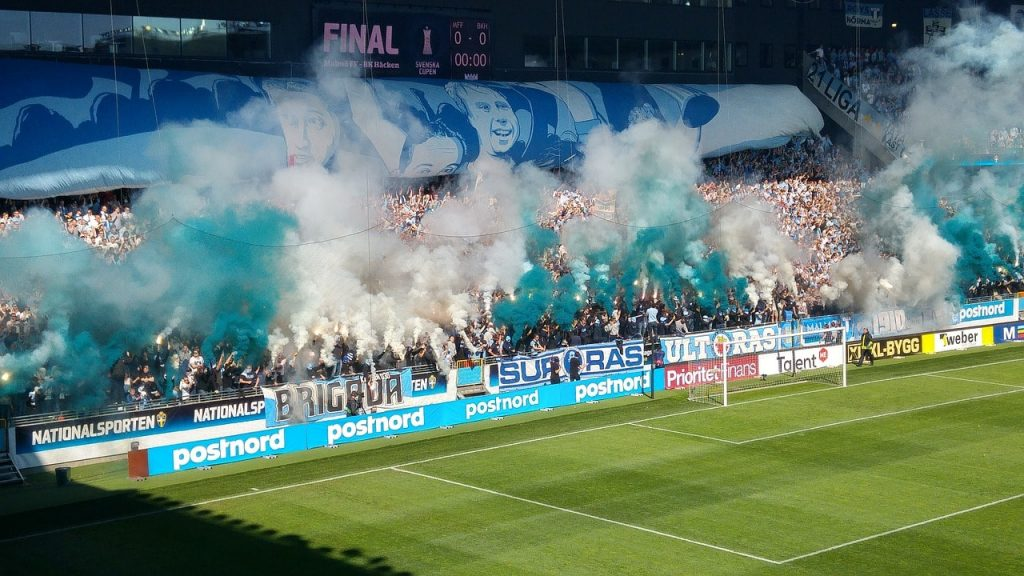 Soccer fans letting off pyrotechnics.