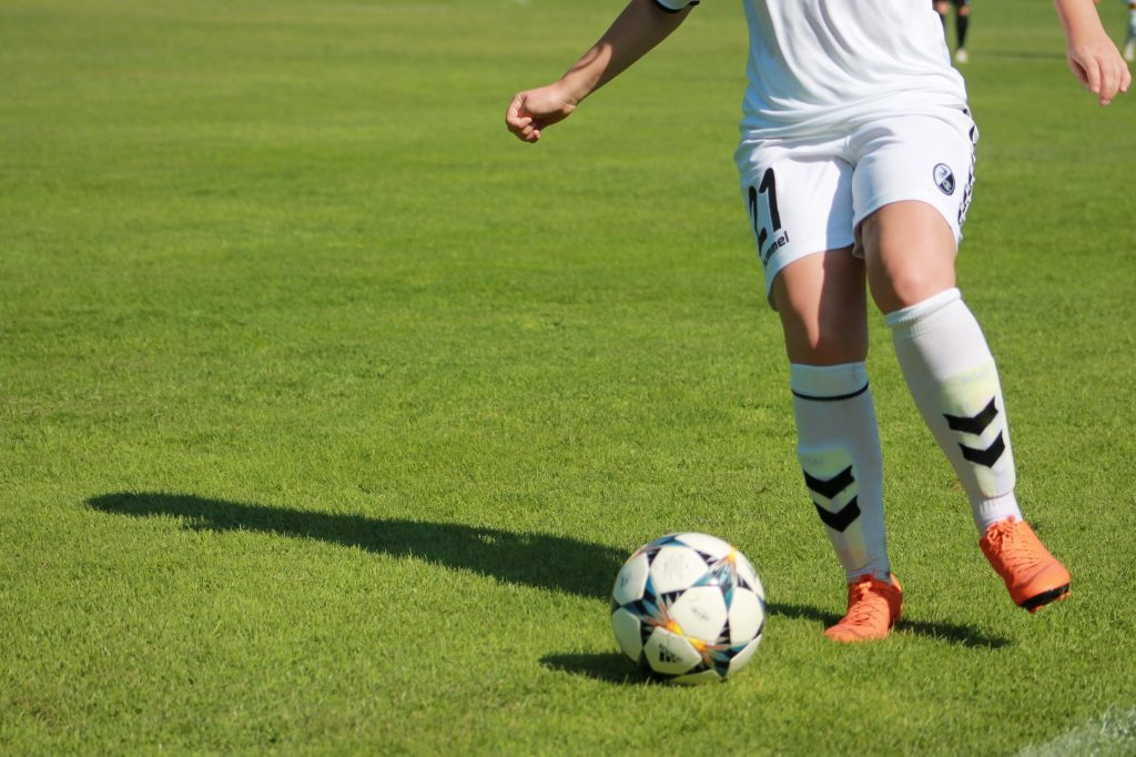 Girl soccer player dribbling the ball.