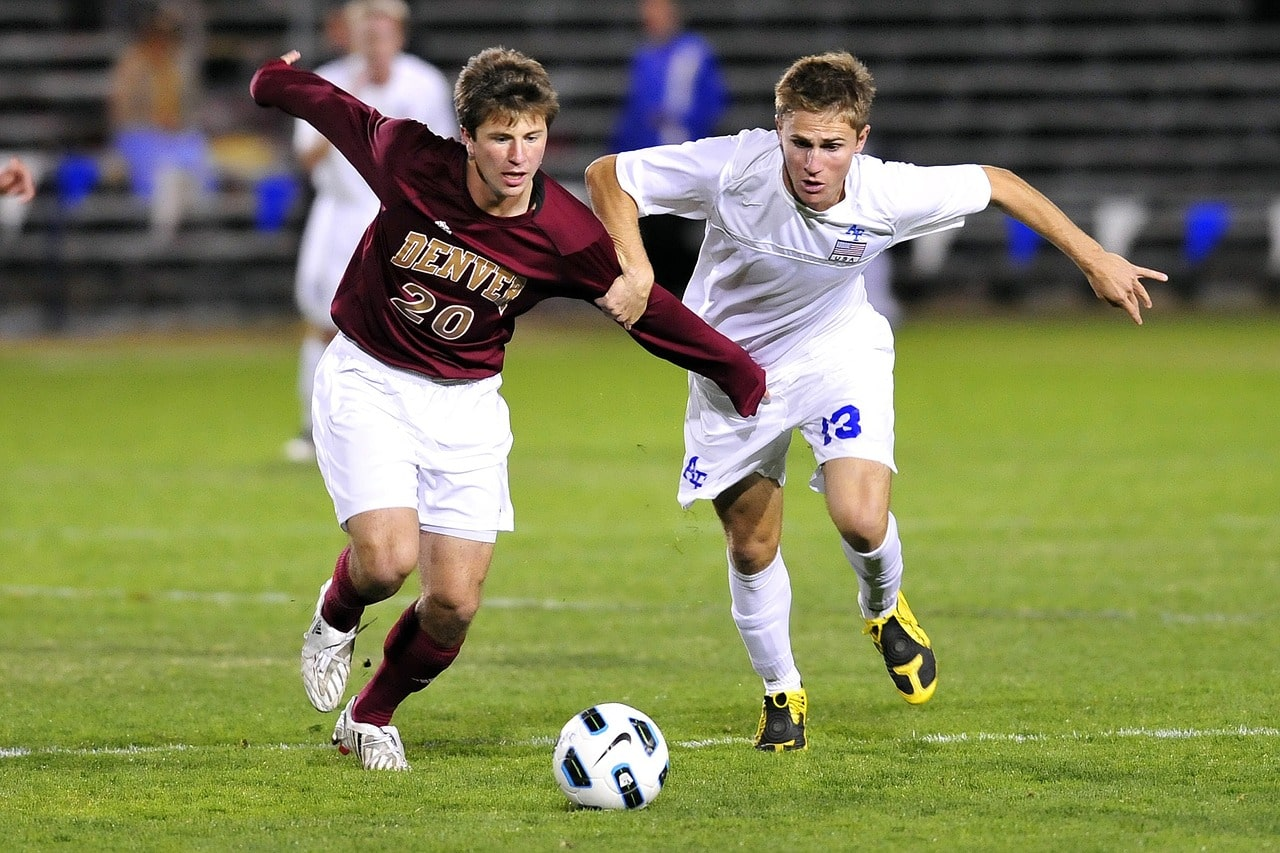 Two college soccer players chasing the ball.