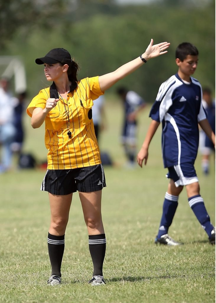 A soccer referee signalling a free kick or a throw-in.