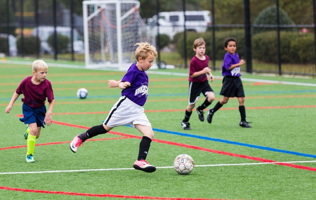 A child playing soccer in turf shoes.