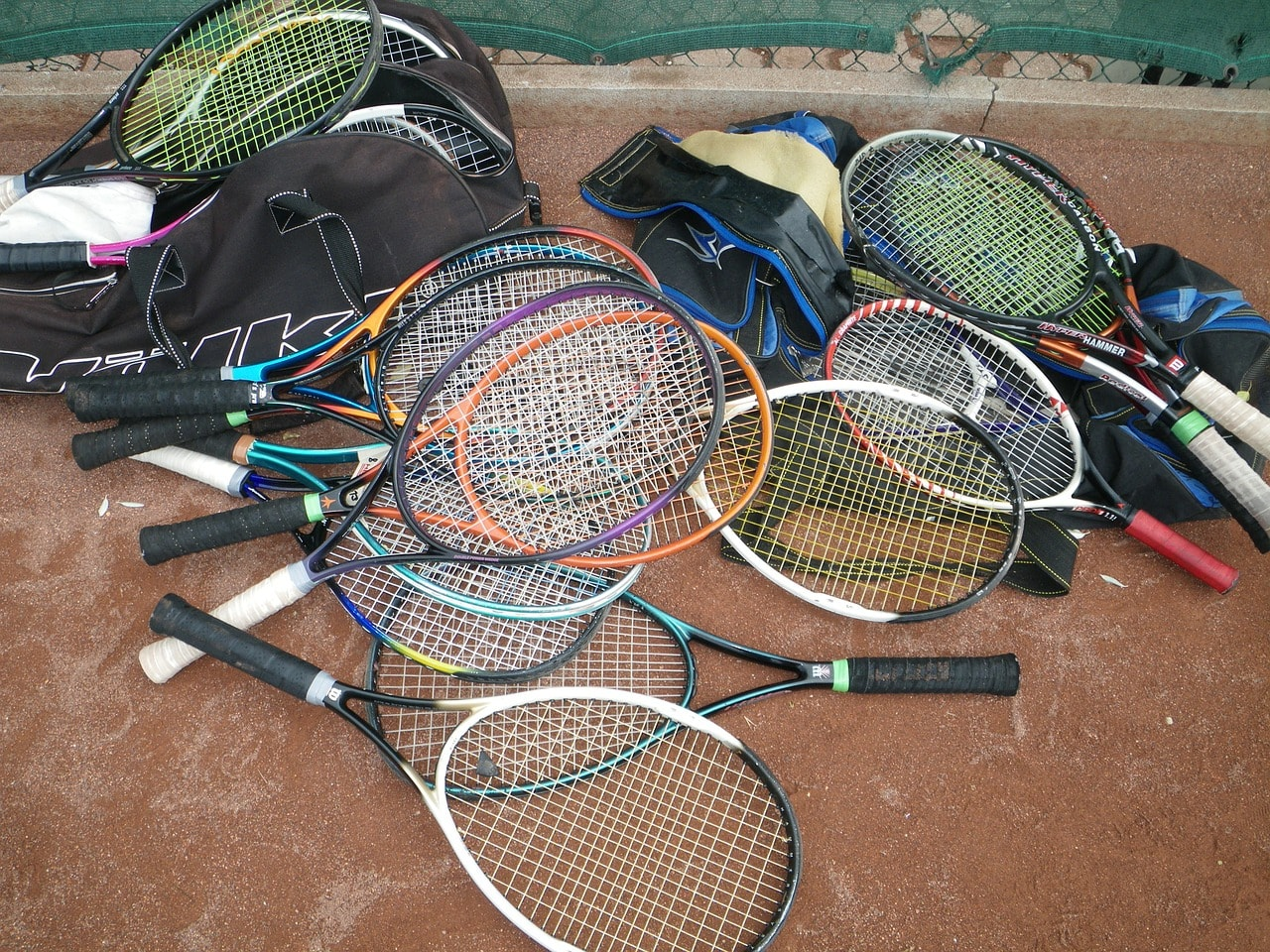 Tennis racquets resting on tennis bags.