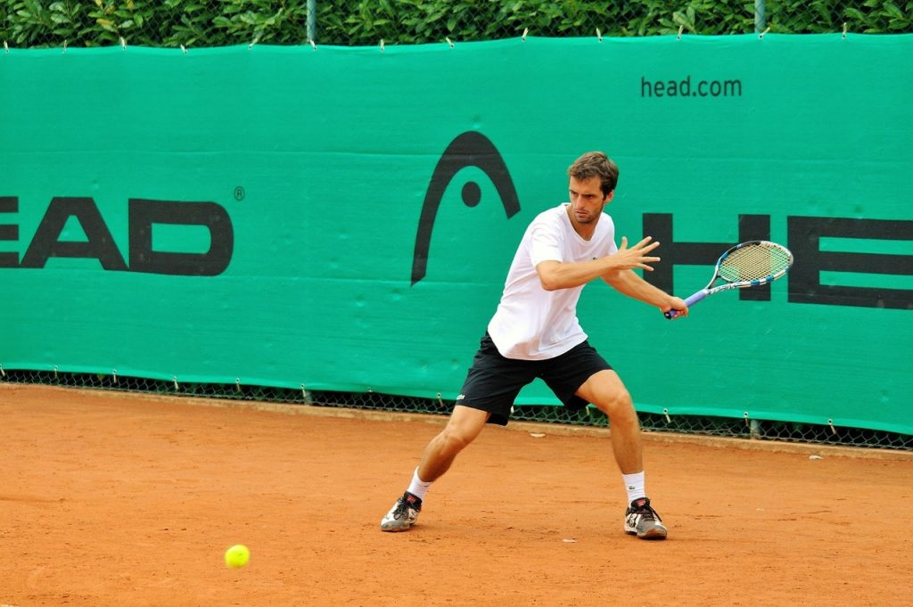 A tennis player wearing tennis shoes on a clay court.