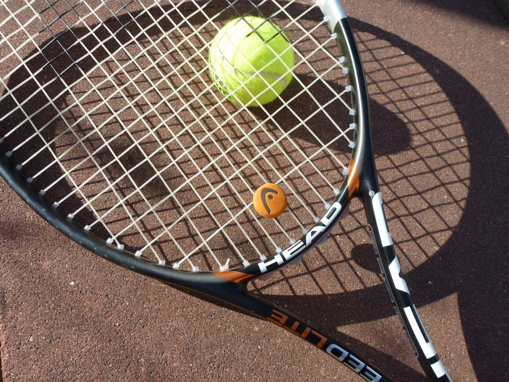 HEAD tennis racket with vibration dampener.