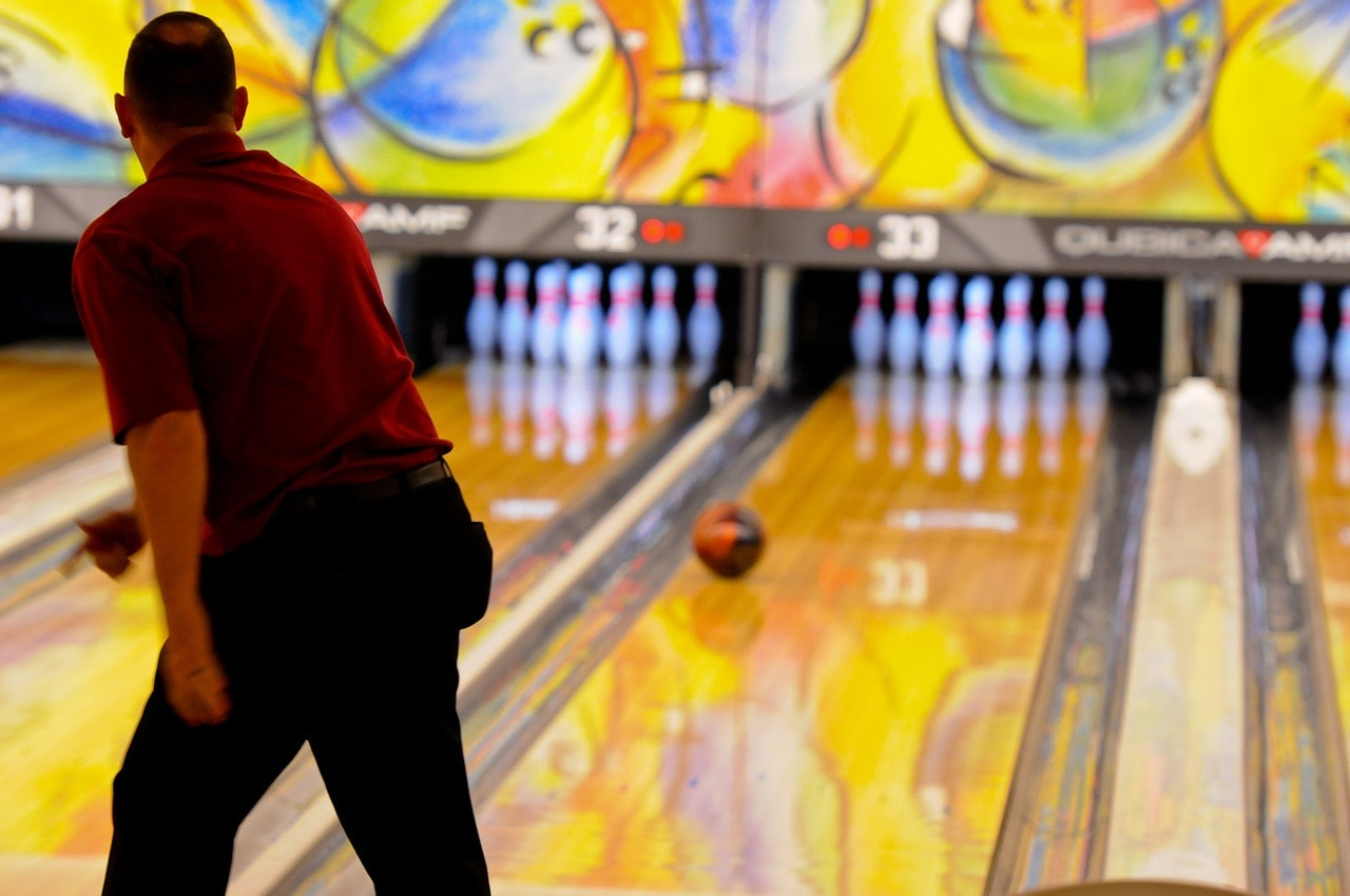 Man playing ten pin bowling.
