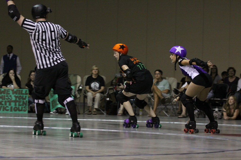 Two roller derby jammers taking a corner.