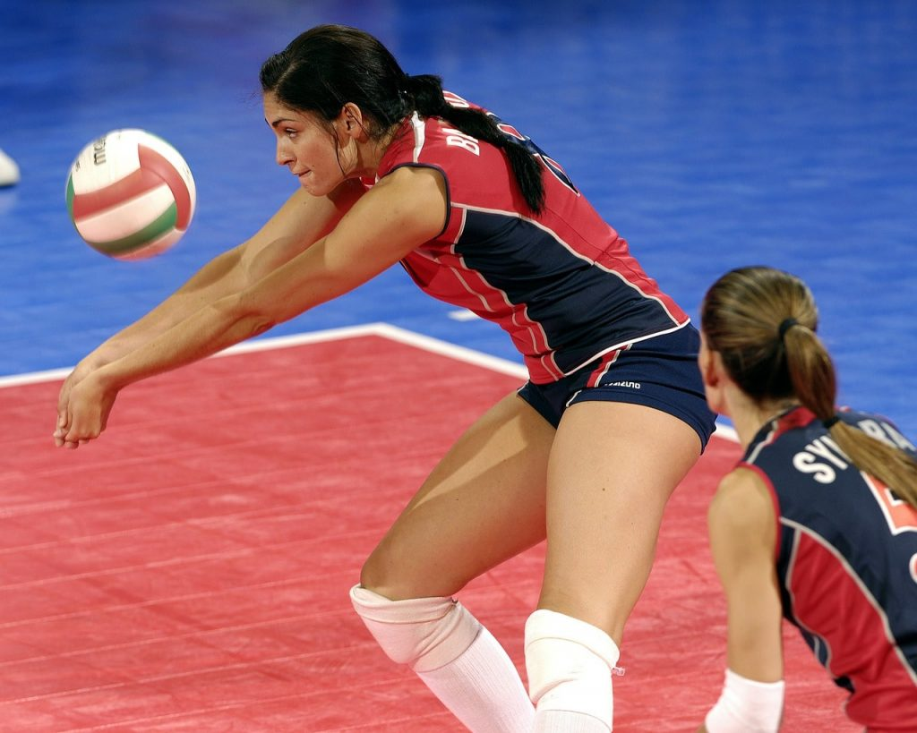 Indoor volleyball player setting the ball.