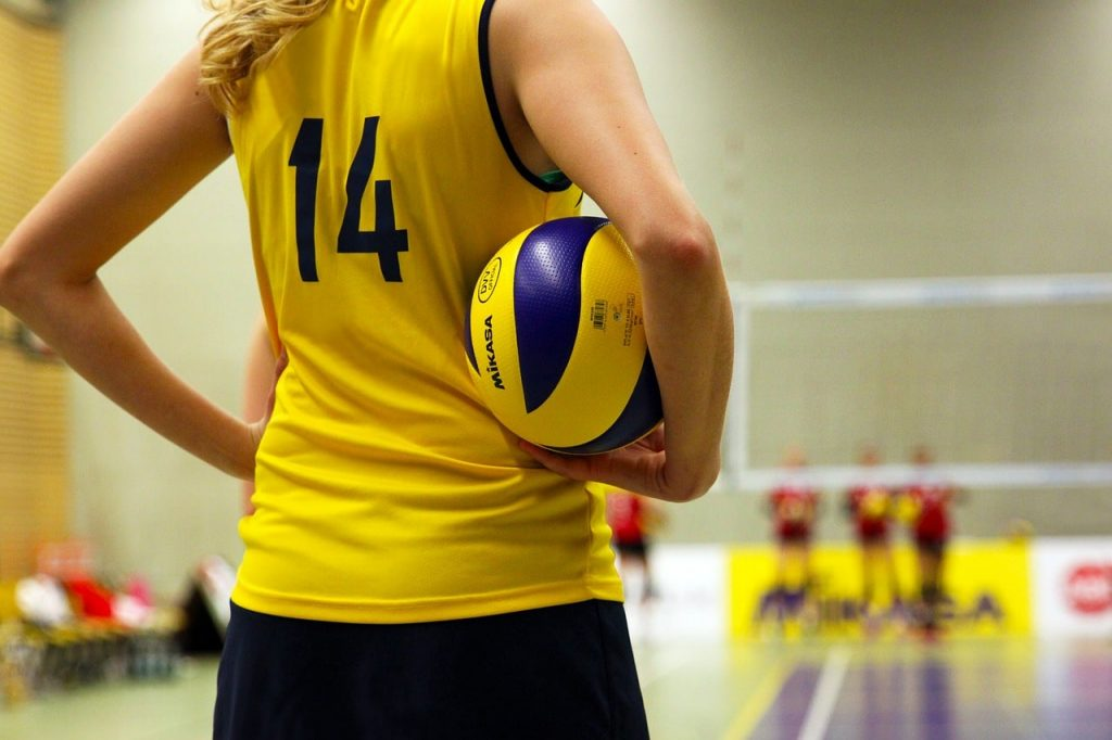 Girl holding an indoor volleyball.