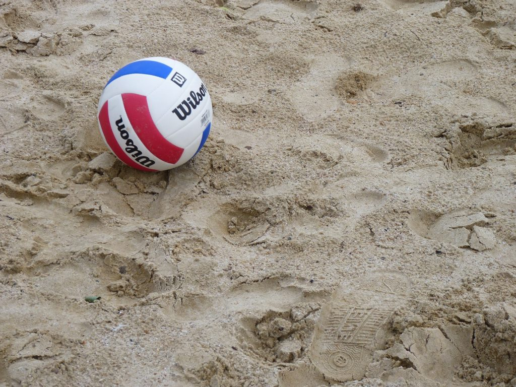 Wilson volleyball resting on sand.